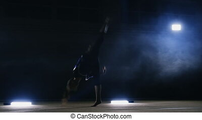 A girl performs a jump gymnastics on a dark background in...