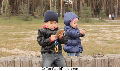 A girl picking pine cones and putting them on the fence where a boy is sitting who pushes buttons in the smartphone.