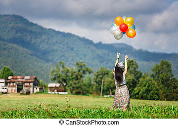 A girl playing balloon in grass field