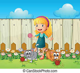 A girl playing with her cats inside the fence