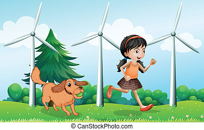 A girl playing with her dog near the windmills