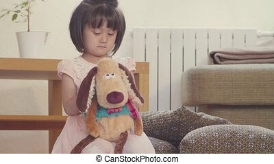 A girl playing with stuffed dog
