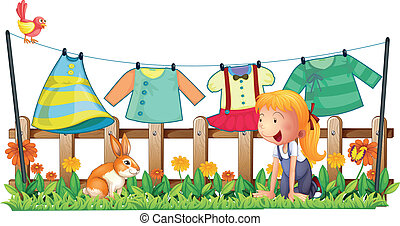 A girl playing with the bunny at the garden with clothes