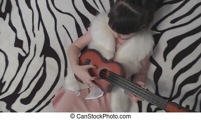 A girl plays in a child's guitar. The view from the top