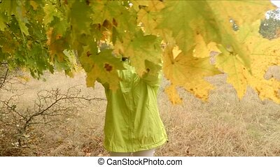 a girl plucks foliage, dew