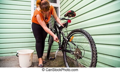 A girl prepares a bicycle for the season. She wipes the moss...