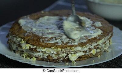 A girl prepares a liver cake for a holiday, smears...