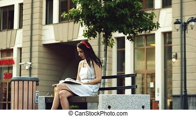 A girl reads a book in the park while smoking and starts yawning.
