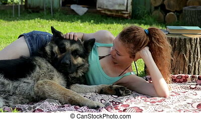 A girl rests with a dog on the grass