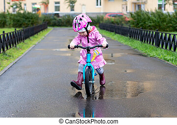 a girl rides a small Bicycle on a wet road