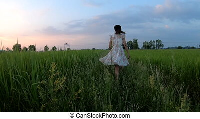A girl running slow motion in the rice field at sunset