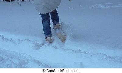 a girl runs across large snow drifts