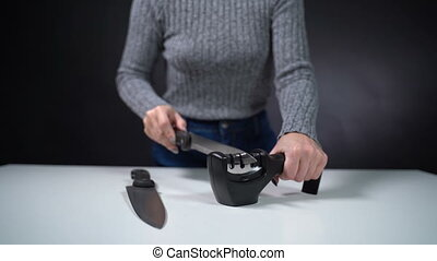 A girl sharpens a knife with a sharpener on a white table