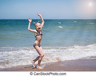A girl sings a merry dance in the sun by the sea.