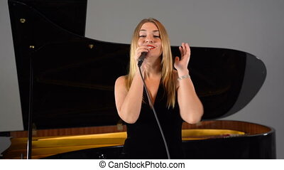 A girl sings into a microphone on stage