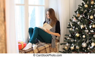 a girl sits by the window and reading a book new year