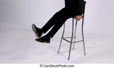 A girl sits on a high chair and dangled his legs