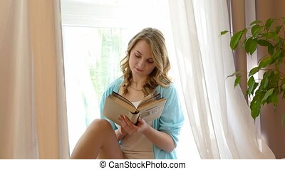A girl sits on a window and reads a book - Attractive girl...