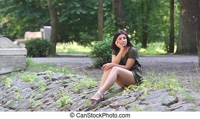 A girl sits on rocks in a recreation park