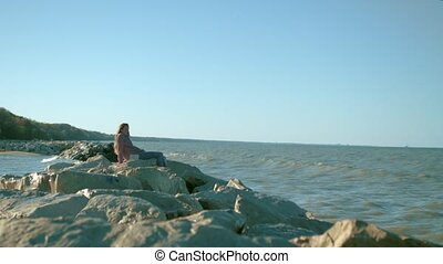 A girl sits on the rocks on the background of the sea.