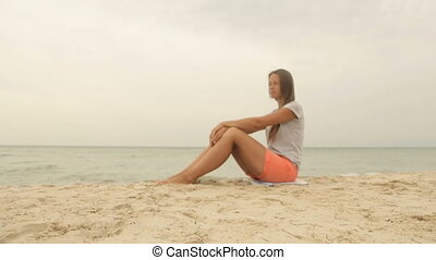 A girl sits on the sand and looks at the sea