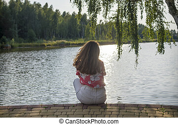 A girl sits on the shore of a lake at sunset