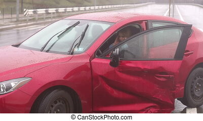 A girl sitting in a broken car after a car accident on a wet road in the rain.