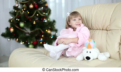 A girl sitting near Christmas tree