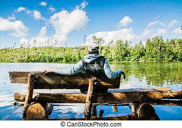 a girl sitting on a rural wooden bench in front of the summer pond