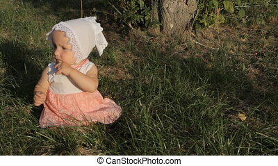 A girl sitting on the grass in a white and pink dress and a bonnet, opening her mouth a rubbing her nose with fingers.