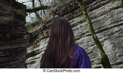 A girl slowly walks in the mountain labyrinth, back view