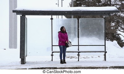 A girl stands at the bus stop in winter