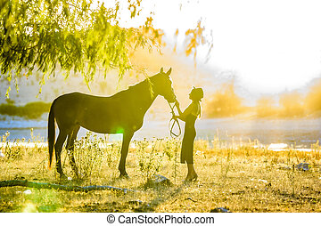 A girl stands in front of a horse on the shore of a lake and is flooded with warm sunbeams at sunset