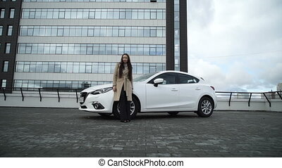 A girl stands near the car