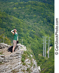 A girl stands on a cliff against the background of green forest