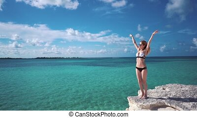 A girl stands on a rock against the azure water of the...