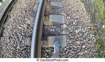 A girl steps on railroad sleepers - Girl steps on railroad...