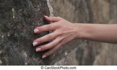 A girl strokes her hand on a stone wall