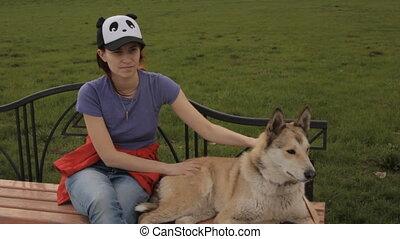 A girl stroking a dog.