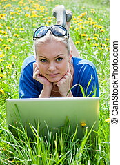 A girl student with a laptop in the park