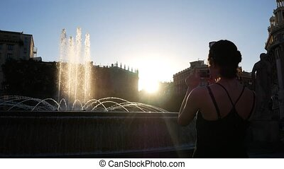A girl taking pictures of european showplace with fountain....