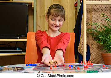 A girl throws large dice making another move while playing a board game at the table