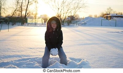 a girl throws snow above her head and falls on snow on sunset background