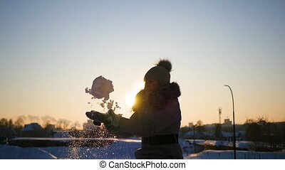 a girl throws snow above her head on sunset background