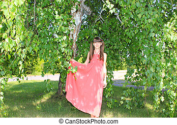 A girl under the birch holds