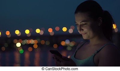 A girl uses a sartphone at night against the background of the city