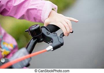 a girl uses the handbrake on a Bicycle