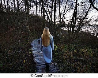 A girl walking along an old wooden path along the shore of a lake