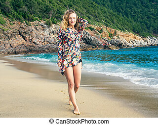 A girl walking along the beach