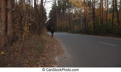 A girl walking along the roadside. And getting out of the frame.